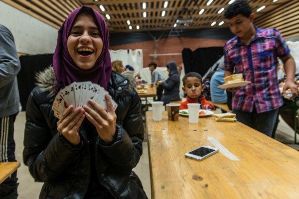 Sura Al Najm (13), a refugee from Baghdad, shows card tricks at her emergency shelter in Friedrichshain, Berlin. Photo Felix Gaedtke.