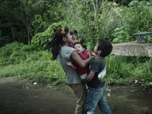 Lilian and her brother play with her son Luis David and their cousin who is also a baby. Twelve years old when she became a mother, she climbs trees, plays soccer and steals fruit from a neighbor's trees whenever she is relieved of her obligations as a mother.