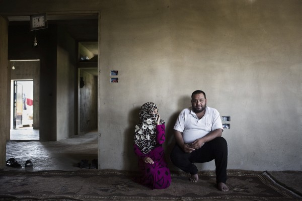 Nour, 13, sits with her 27-year-old husband inside their dwelling in Jeb Janine, Bekaa Valley. Nour and her family, who are refugees from Raqqa Governorate, fled their homeland four years ago.