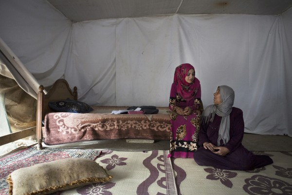 Sumayya, 14, sits with her mother inside their tent shelter in Jeb Janine, Bekaa Valley. The adolescent refused to get married, and her mother decided not to force her.