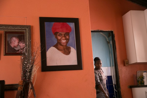 Ayanda Magoloza in her home in Thokoza. Photos on the wall: her mother who passed away a few years back and the photo taken by photographer Zanele Muholi of her and her wife, Nhlanhla.