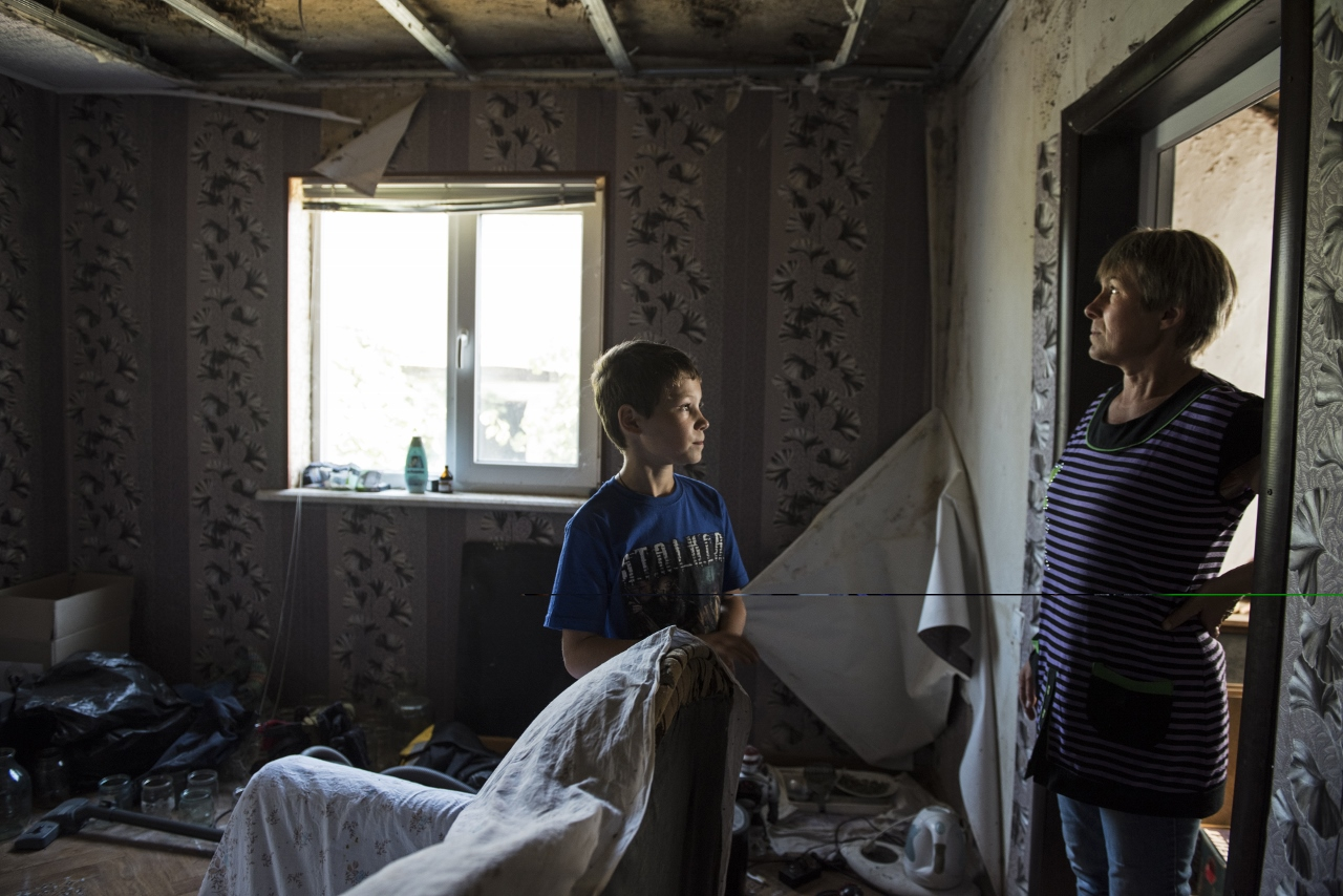 Oleg Teryokhin stands with his mother, Galina Teryokhina, in their home in Nikishino village, destroyed by the east Ukraine war, September 27, 2015, in DNR territory. Nikishino village was far from the sites of early skirmishing and neither side bothered trying to control this small village until it turned out it was on the path of a major Ukrainian offensive begun in July with the goal of encircling Donetsk city, the provincial capital. Using long-range artillery and spotter aircraft to target it, the Ukrainian army was pushing separatists back from one town after another. Galina Teryokhina, Oleg's mother, said residents didn't take the war seriously until mid July, 2014. Oleg was playing outside in the afternoon when loud explosions were heard in the sky. Later, some papers with English writing and bits of charred clothes fluttered through the village, and Oleg picked some up. Nikishino village was at the edge of the debris field of the Malaysia Airlines Flight 17, likely shot down by rebels who mistook it for a Ukrainian spotter aircraft. Photographs by: Lynsey Addario/Getty Images Reportage