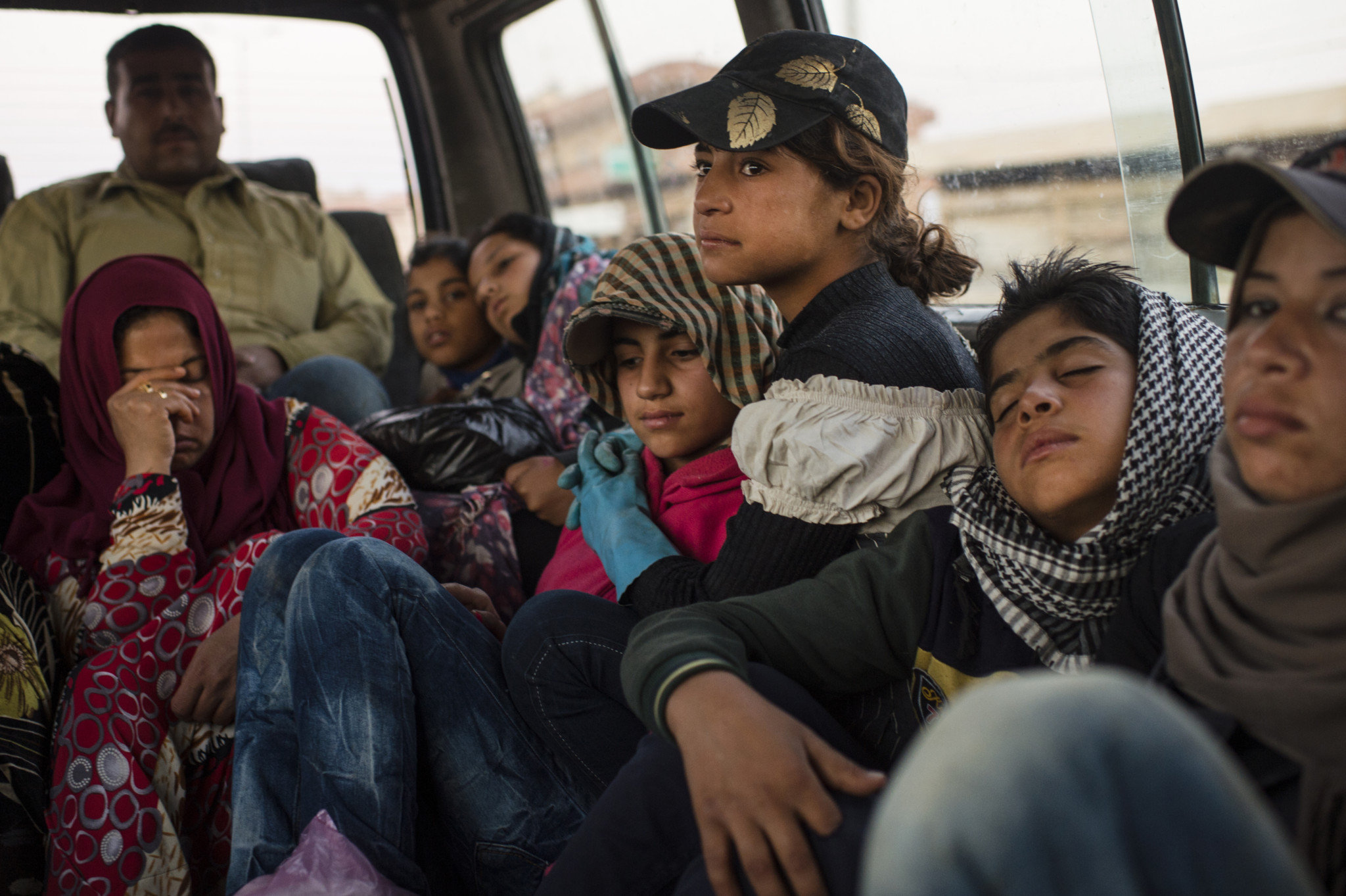 Hanaa rides to work at plum orchard before dawn along with other Syrian refugees from her informal tented settlement in the Bekaa Valley, between the city of Zahle and Baalbak, in Lebanon, August 3, 2015.  Hanaa and her family fled Syria in 2011 at the beginning of the Syrian civil war, and moved to this settlement two years ago, along with other Syrian refugees from Hasaka and the surrounding areas. Hanaa and other children in the settlement work for up to ten hours a day in agricultural lands owned by Lebanese in the area, and earn the equivalent of $5. per day.  Photographs by: Lynsey Addario/Getty Images Reportage