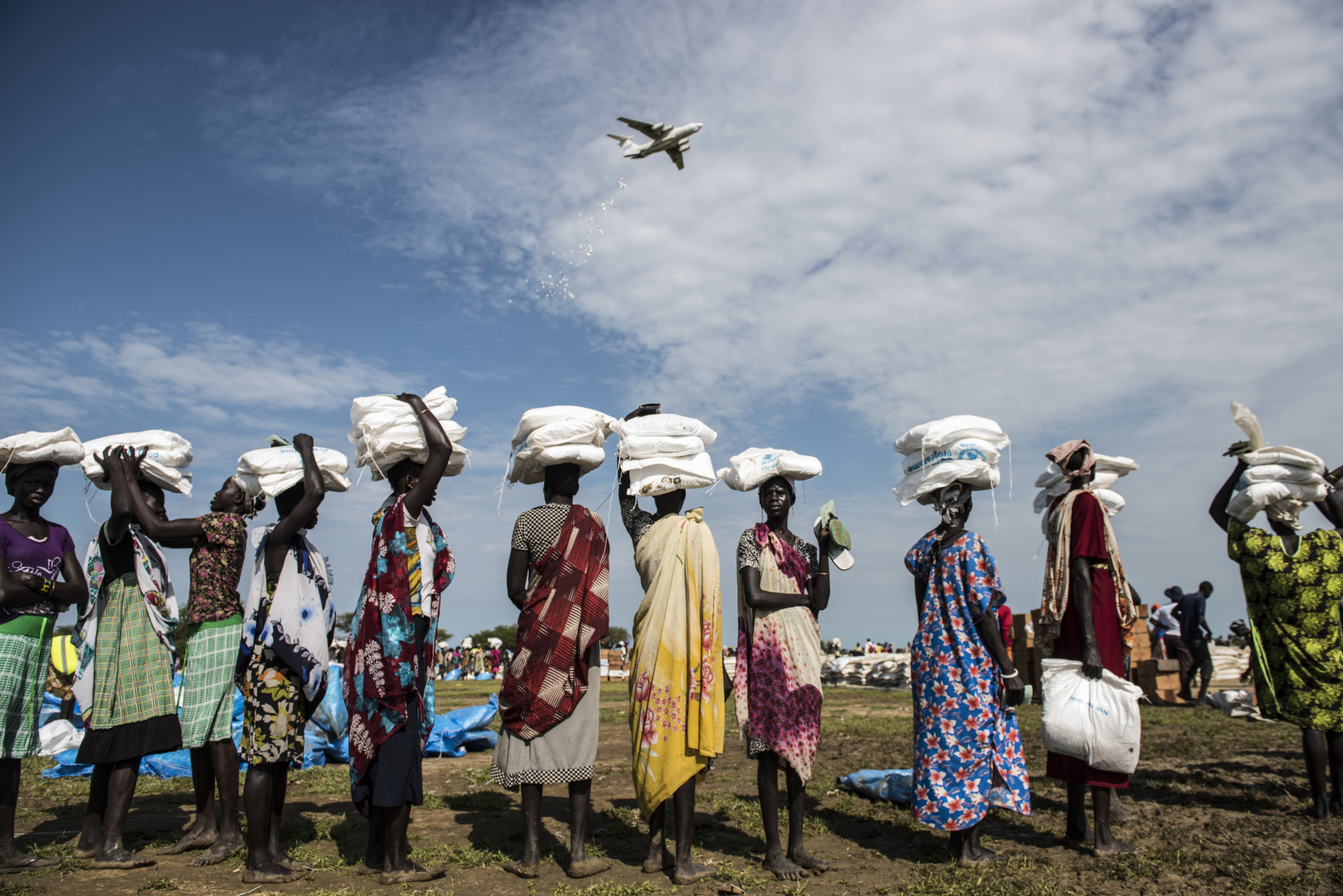 Resilience of Children: Planes with the World Food Program conduct food drops to help aid new internally displaced Southern Sudanese, who were recently displaced from Leer, Mayangi, and Koch to the  area of Nyal, in Unity State, South Sudan, September 10, 2015.  Because of ongoing fighting throughout South Sudan, civilians have been unable to till their land and plant crops, and aid organisations have been unable to deliver food. In a rare window of peace in the area, WFP has been dropping TK tons of food in Nyal for locals and surrounding villages.   Chuol, 9, from southern Unity State or outside Leer, lives within a host community full of local villagers and other internally displaced with his grandmother and sister. several months ago, his own village was attached, and his father and grandfather were burned alive. He, his grandmother, and sister fled to this area, where they are living on the ground of a host family. (lynsey Addario/Getty Images Reportage)