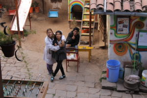 Coordinator Andrea hugging one of the older students, 15 years old, in the courtyard and playground of Aldea Yanapay
