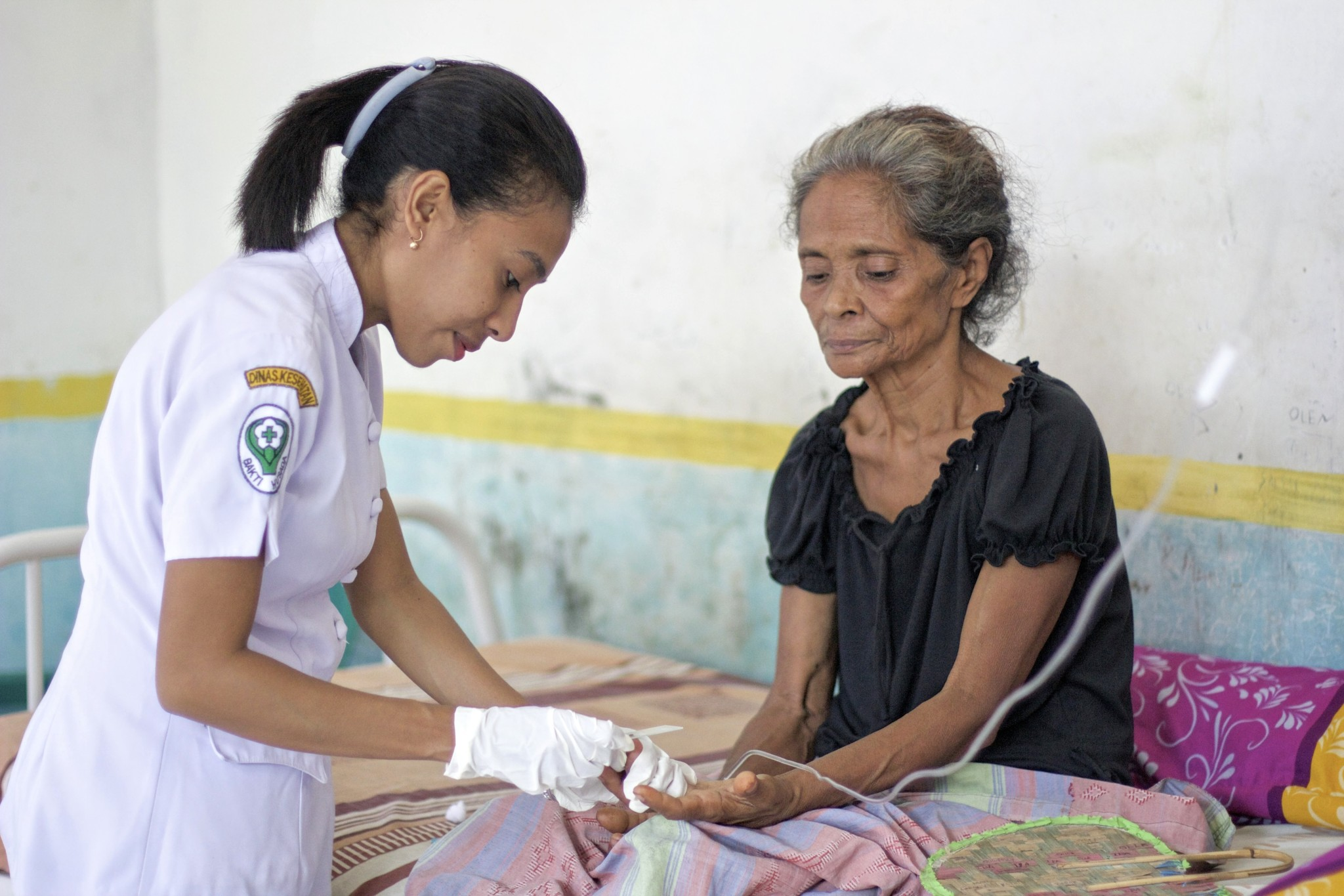 "56-year-old Fransura Kavori recovers from an attack of Plasmodium falciparum malaria at the Mebung Primary Health Centre at remote Alor Island in eastern Indonesia. Her nurse, Dian Adiana of the Ministry of Health, takes a follow up blood sample to check on the progress of her therapy against the infection. Ms. Kavori happens to be the malaria volunteer worker and traditional healer of her home village. Traditional healing is a very important element of healthcare in Indonesia, with many dozens of defined herbal remedies for common ailments collectively referred to as ""jamu"". Traditional healers, however, acknowledge and understand their limits, as Ms. Kavori's presence at hospital demonstrates. Malaria is well known to be out of the healing reach of traditional jamu."