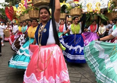 At the Desfile de Delegaciones, lines of women from Chinas Oaxacañas dance through the street with baskets of bread balanced on their heads. Every few minutes, bread from the baskets is thrown to the crowd, part of the Guelaguetza tradition of giving.