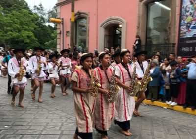 A group of saxophonists walk ahead of their delegation during the Desfile de Delegaciones, signaling to onlookers that traditional dancing will follow.