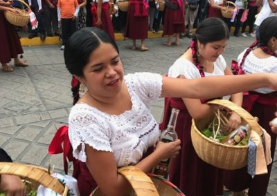 During Saturday's Desfile de Delegaciones,(Parade of Delegations), indigenouswomen enact the festival's theme of giving by passing out small cups of mezcal and produce from their region.