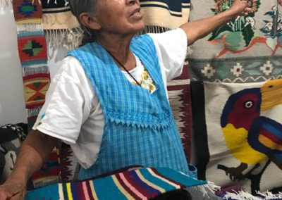 A vendor from Santa Ana del Valle explaining her products' designs to a prospective customer at the central artisanal market of Guelaguetza
