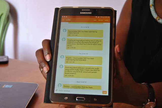 A volunteer at the Wangu Kanja Foundation shows how they receive messages from the the Helpline on her tablet.