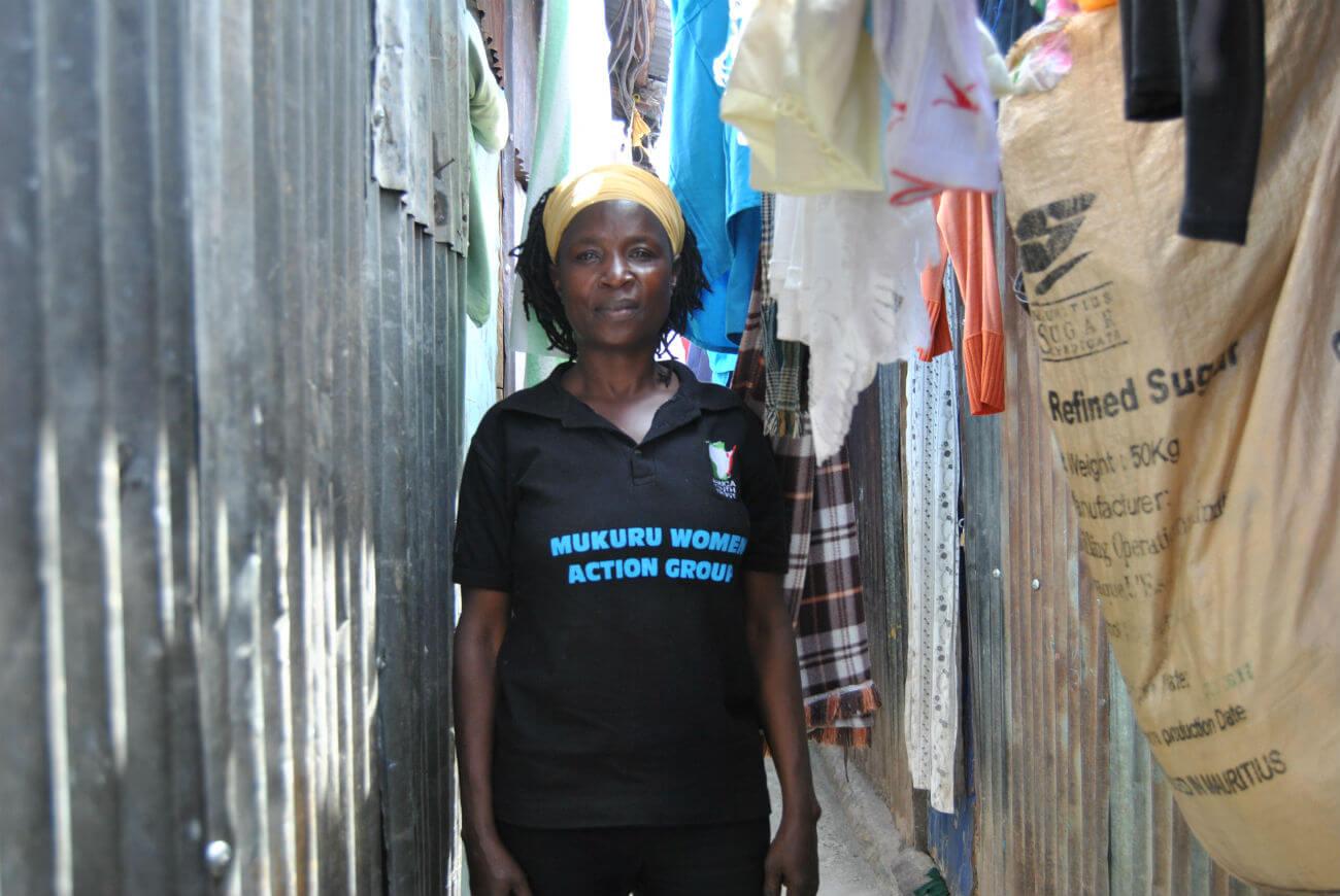 Eunice Akinyi poses for a photo outside her house in Mukuru Kwa Reuben slums before she heads back to work.JPG