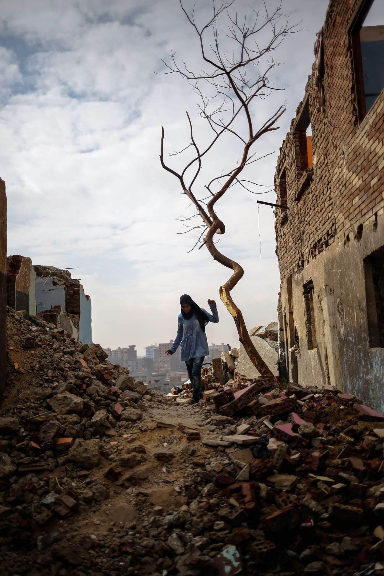 Yara picks her way through the rubble created by fallen-down buildings in Khairallah. Credit: Plan International / Heba Khalifa