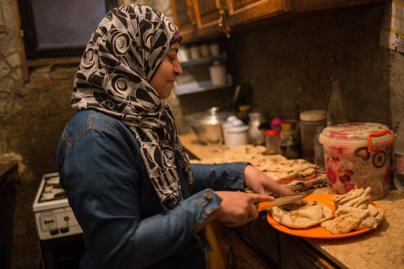 Yara's mother Aisha prepares food for the family at home in Khairallah