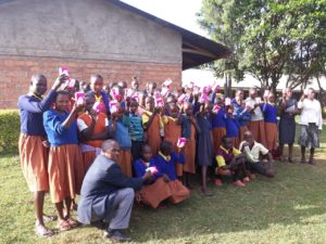 Pupils and teachers of Kenyagoro Primary school hold sanitary towels supplied to them by Integrity Counselling and motivational Consultancy